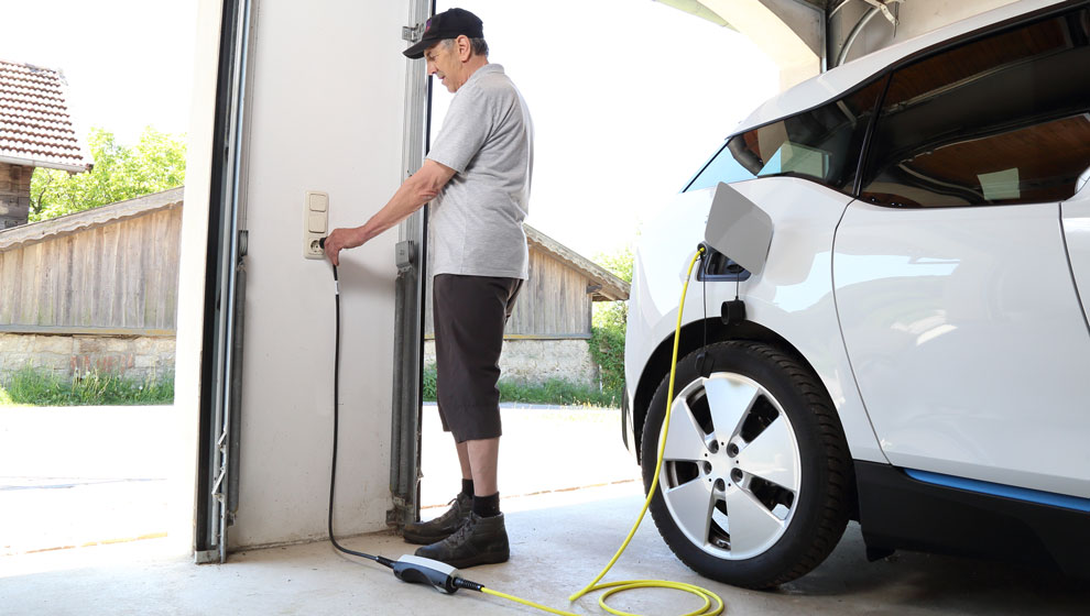 ev-charging-report-man-charging-electric-car-garage-990x560.jpg
